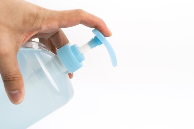 アジアのマンドの手は、ゲルアルコールポンプボトルを保持し、それを押す準備ができています