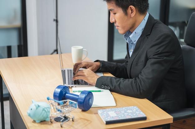 노트북 및 제품 돼지 저금통, 아령, 사무실에서 나무 책상에 미니 쇼핑 카트를 사용하는 아시아 마케팅 관리자 남자