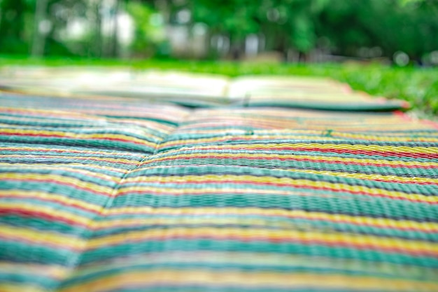 Asian mat on the grass ground in the outdoor park without people.