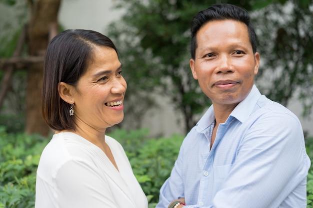 Азиатский зрелый любовник улыбаться вместе на открытом воздухе во время отпуска на день святого валентина