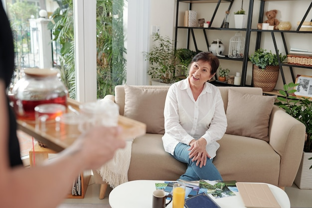 Asian mature woman sitting on sofa and waiting for tea during her visit to friend at home