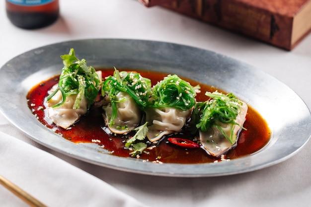 Азиатские пельмени с мясом и соусом в миске