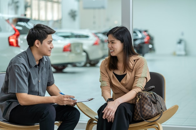Asian mechanic explaining the check list of maintainance service to customer in showroom
