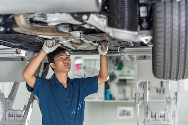 Азиатский механик ремонтирует и загорается под автомобилем в сервисном центре обслуживания
