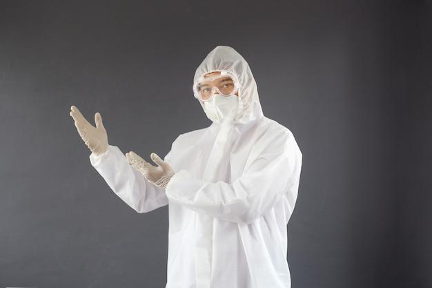 Азиатский медик в защитном медицинском костюме показывает руку, чтобы скопировать пространство слева