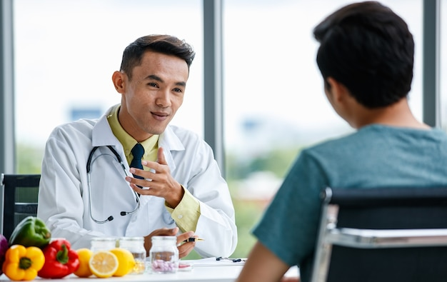 Asian medical practitioner give information and advice and explaining prescription to man patient during work in hospital