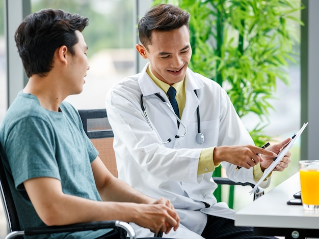 Asian medical practitioner pointing at clipboard and explaining prescription to man during work in hospital