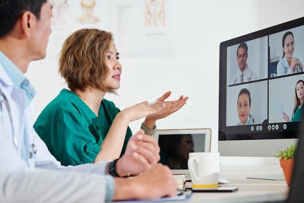 同僚とオンライン会議を行い、コロナウイルスを治療する最新の方法について話し合うアジアの医療従事者