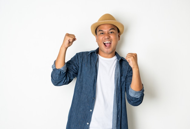 Asian men aged around 30 wearing hats and jeans feeling happy celebrate with two hand stretch on white background.