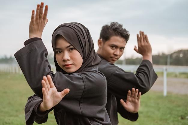 Pencak silat 유니폼을 입은 아시아 남성과 여성이 조수 움직임으로 서 있습니다.
