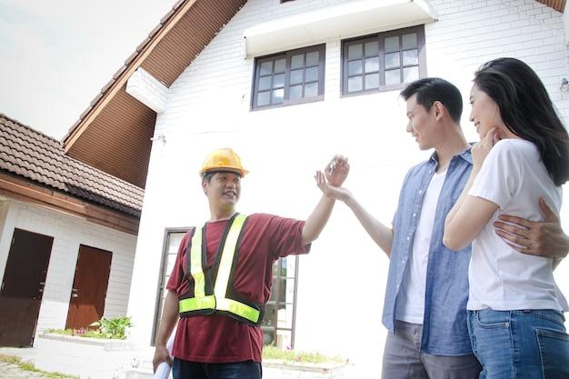 アジアの男性と女性のカップル家の検査エンジニアから家の鍵を入手してください。彼らは両方とも彼らの新しい家に満足していた。家族を始めるという概念。