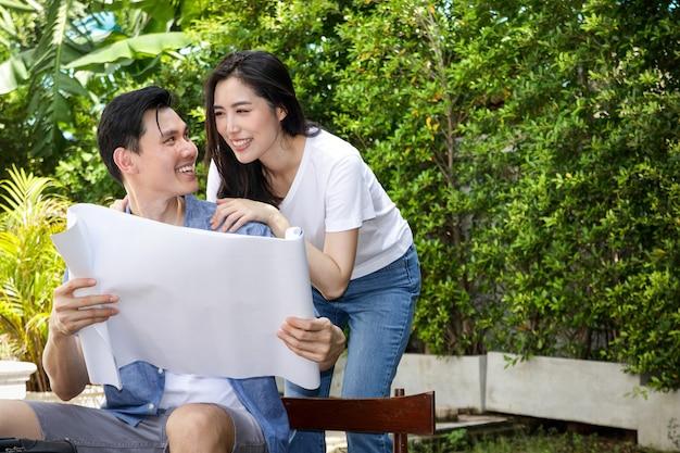 새 집을 짓기 위한 종이 청사진을 들고 있는 아시아 남녀 커플들은 함께 가족을 짓게 되어 기쁩니다. 결혼 생활을 시작하는 개념 행복한 가정을 꾸십시오.