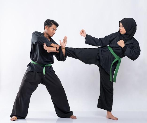 プンチャックシラットの制服を着たアジアの男性と女性が戦う