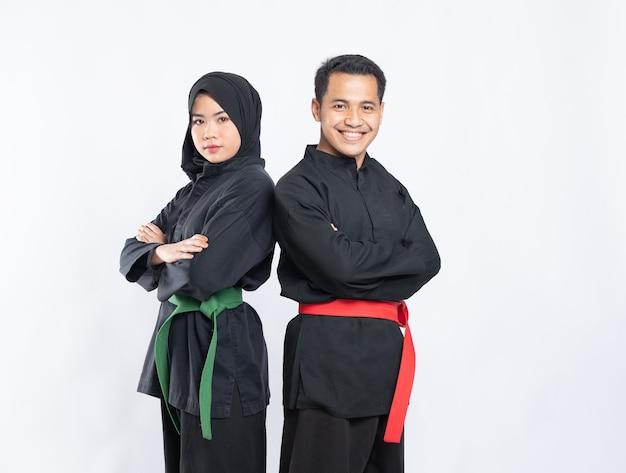プンチャックシラットのユニフォームを着たアジアの男性と女性が背中合わせに立っています