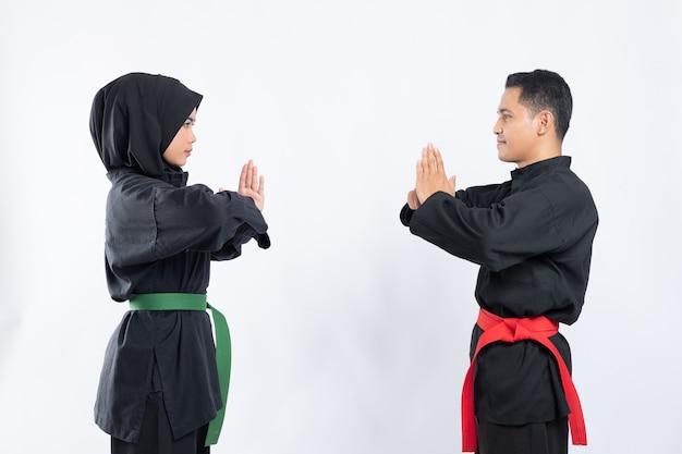 Pencak silat 유니폼을 입은 아시아 남성과 여성이 존경심으로 얼굴을 맞대고 서 있습니다.