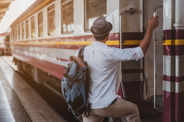 Азиатские мужчины садятся на поезд, чтобы поехать на каникулы. праздник, путешествие, поездка и летняя концепция путешествия.