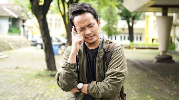 アジア人男性はバッグを着て混乱しています