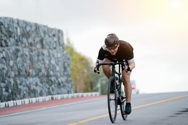아시아 남자는 아침에 도로 자전거를 자전거