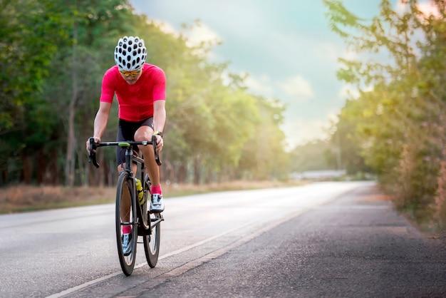 아시아 남자는 일몰 시간 동안 아스팔트 도로에서 자전거 도로를 자전거