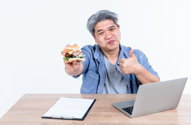 Asian men are enjoying eating hamburgers while he was working by using a notebook computer