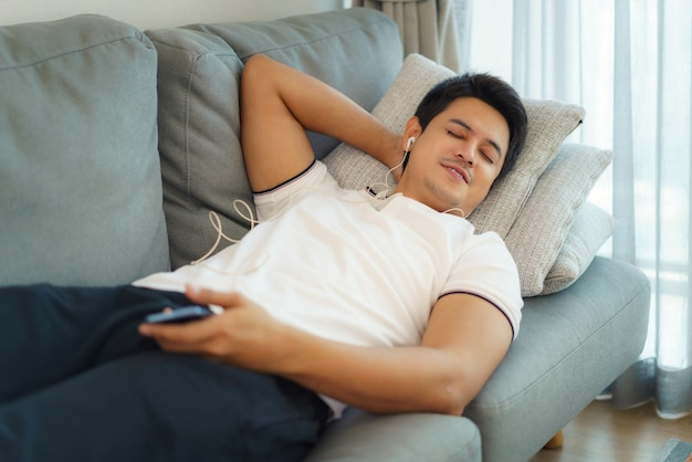 アジア人男性は、自宅の居間のソファでヘッドホンを使って音楽を聴いて休んでいます。