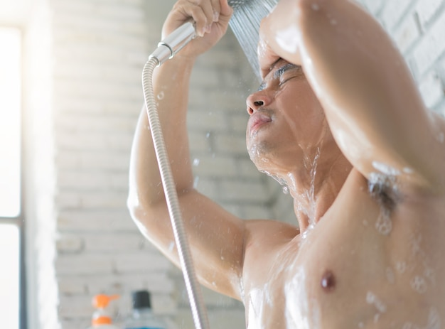 Asian men are taking a shower in the bathroom, he is happy and relaxed