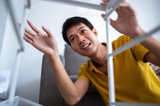 自宅の居間で家具を組み立てるアジア人男性。