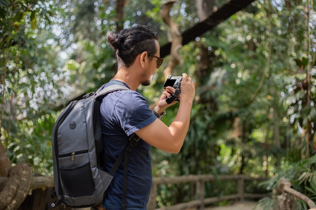 Asian men backpacks and traveler walking together and happy are taking photo on forest, relax time on holiday concept travel