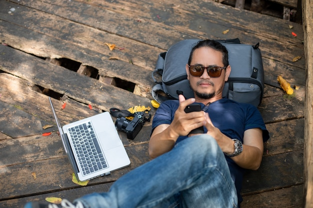 Asian men backpacks and traveler working on computer laptop at outdoor nature and he is relaxing and enjoying on travel
