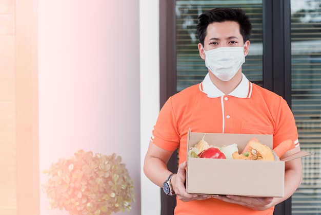 Asian men carry goods wearing an orange shirt handle paper crates that contain vegetables and fruits