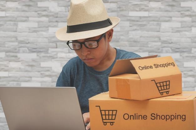 顧客からのオンライン購入のショッピング注文をチェックするアジア人男性。