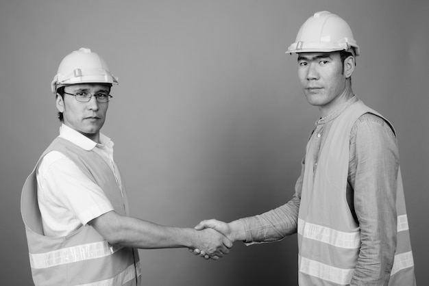 Asian men construction worker together isolated