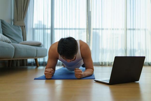 アジア人男性は、covid-19の発生時にジムの閉鎖で板張りをすることにより、自宅で運動します。