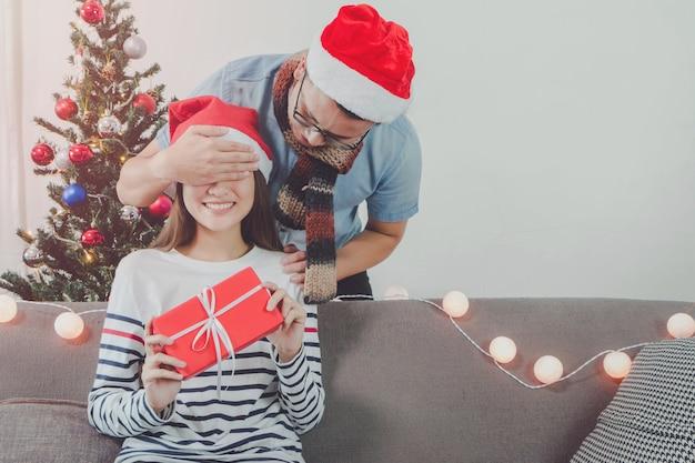 アジアの男性は、美しい若いアジアの女性にギフトボックスを与える。休日の背景のためのクリスマスツリーの装飾と部屋の顔を満たす。恋人カップルとお祝いの概念。