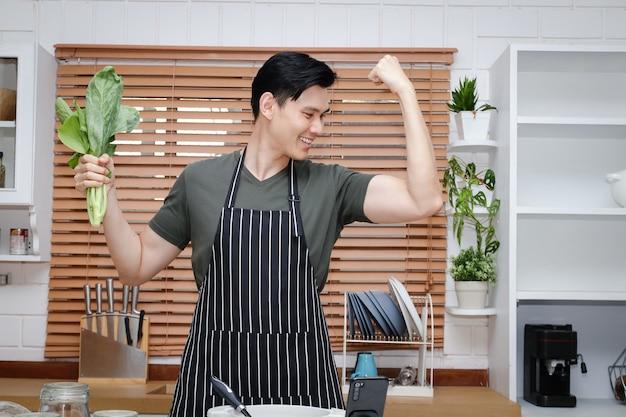 아시아 남자는 집에서 부엌에서 요리의 즐거움을 가지고