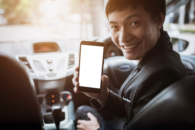 Asian men holding a mobile phone while driving a car.