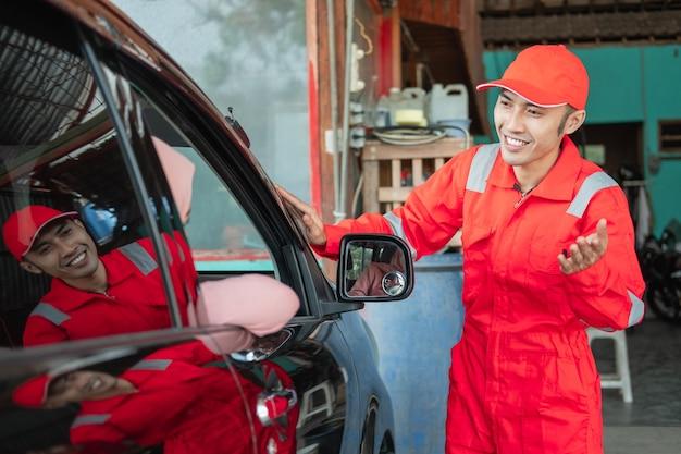 顧客がワークショップで修理のために車で来るとき、赤い制服を着たアジア人男性が歓迎のジェスチャーで挨拶します
