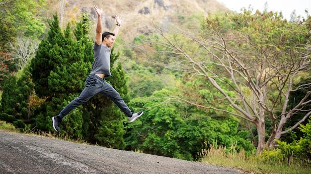 Asian men jumping in a nature garden.