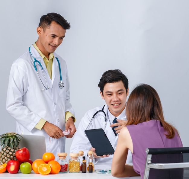 Asian men in medical uniform talking with woman and making notes near table with healthy food in modern clinic