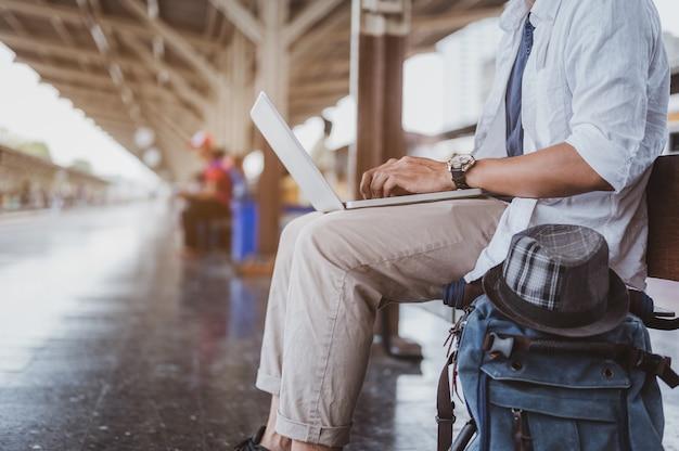 Азиатские мужчины используют свой ноутбук для работы, ожидая сесть на поезд для путешествия. праздник, путешествие, поездка и лето концепция путешествия.