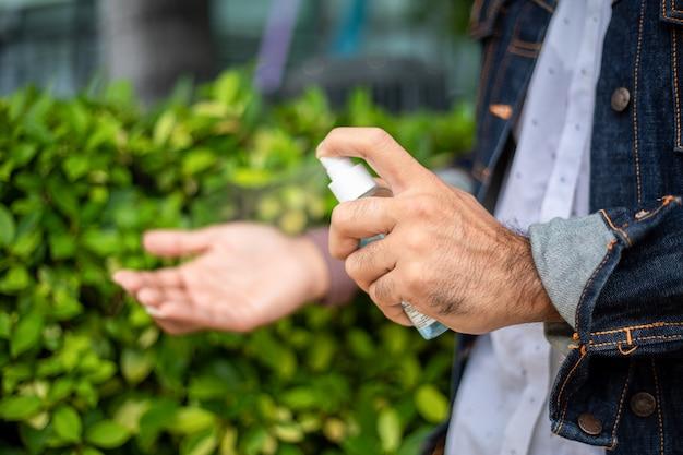 インフルエンザやウイルスの予防対策にアルコールスプレーとアルコールジェルまたはローションを使用しているアジア人男性