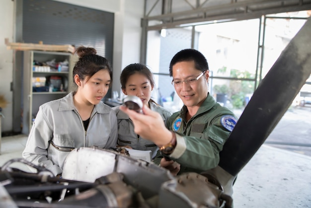 Asian men and women engineers and technicians are repairing aircraft.