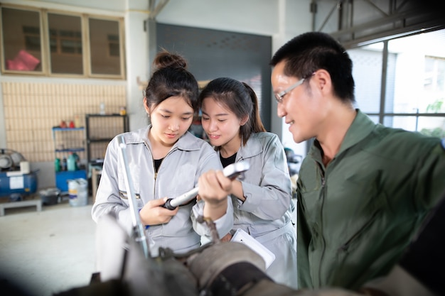 Asian men and women engineers and technicians are repairing aircraft