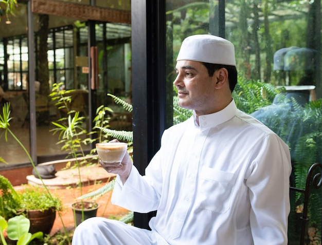 Asian mid aged muslim business man sit in coffee shop drink coffee with mobile phone on table.