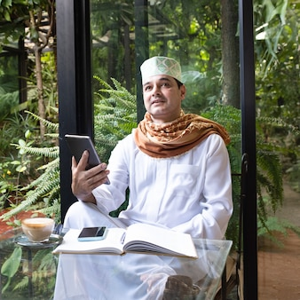 Asian mid aged muslim business man sit in coffee shop drink coffee with smart mobile phone on table.
