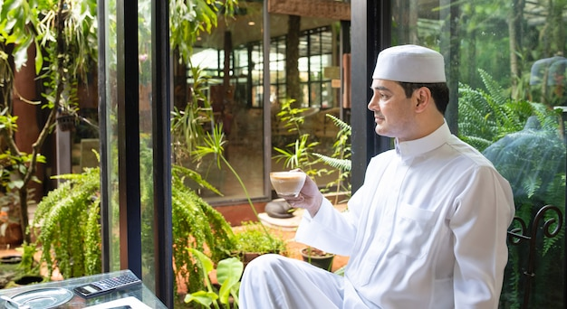 Asian mid aged muslim businessman sit in coffee shop drink coffee with smart mobile phone