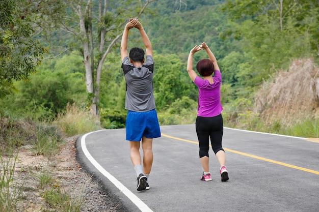 公園でジョギングする前に筋肉を伸ばすアジアの中年夫婦