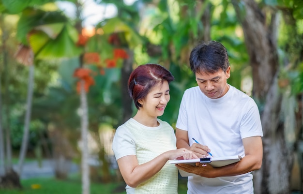 Asian middle-aged couple talking and designing garden plan together in backyard.