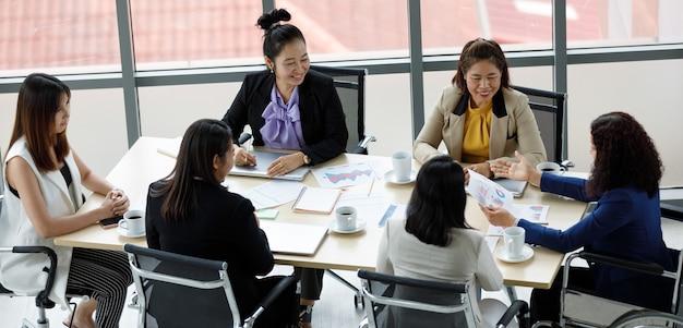 회사 사무실 작업 공간에서 노트북 컴퓨터를 사용하여 다른 직원들과 함께 일하는 휠체어에 앉아 공식적인 업무복을 입은 아시아 중년 여성 장애인 여성 사업가 직원.