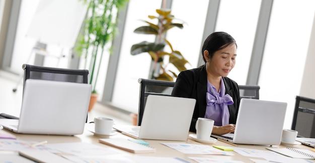 アジアの中年幸せな自信を持って女性の成功した女性秘書は、静かな会社のオフィスの部屋で一人でラップトップノートパソコンで情報を入力するワーキングデスクに座って正式なスーツを着ています。